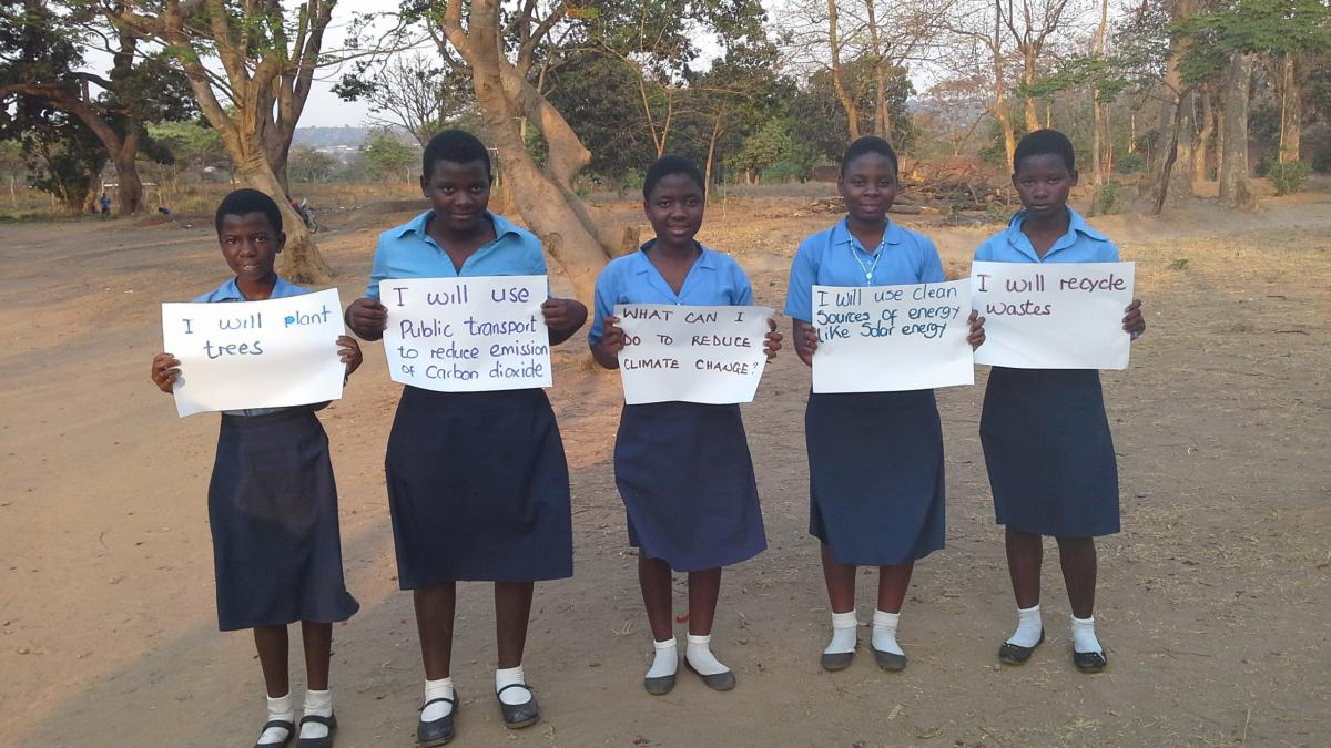 Students at Lilongwe Girls' Secondary School in Malawi hold up signs showing the ways in which they can help to slow global warming (Photo: UNITAR)